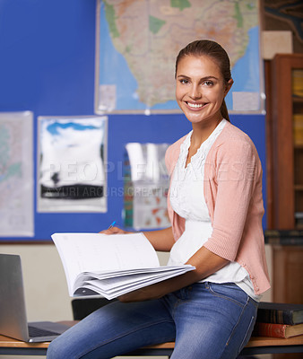 Buy stock photo A beautiful young teacher sitting on the side of a desk holding a book and smiling at the camera