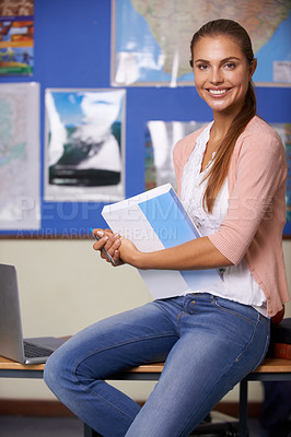 Buy stock photo A beautiful young teacher sitting on the side of a desk holding paperwork - portrait