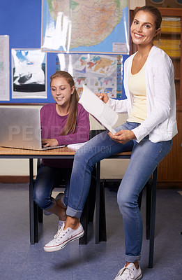 Buy stock photo A young teacher sitting on the side of her pupil's desk and smiling at the camera