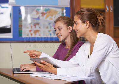 Buy stock photo A young teacher helping her student with a project on her laptop