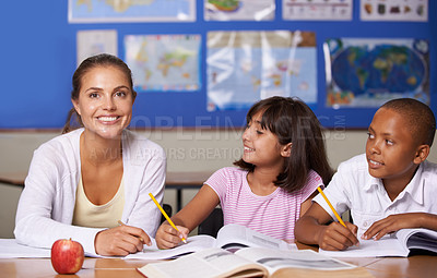 Buy stock photo A young teacher sitting with her two ethnic pupils while they page through a textbook - portrait