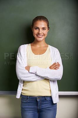 Buy stock photo A lovely young teacher standing in front of a blackboard with her arms folded