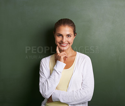 Buy stock photo A lovely young teacher standing in front of a blackboard touching her cheek - portrait