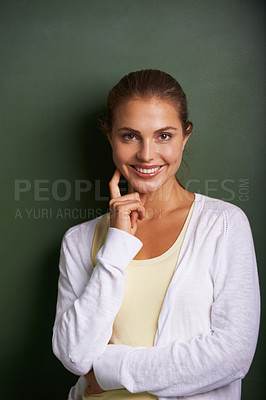 Buy stock photo A lovely young teacher standing in front of a blackboard touching her cheek