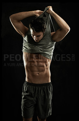 Buy stock photo Muscular young man showing taking off his shirt, revealing his abs