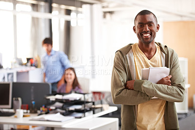 Buy stock photo Shot of a young designer holding his notepad and digital tablet with his colleagues blurred in the background