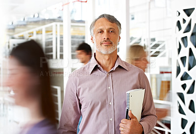 Buy stock photo A handsome mature businessman sitting calmly as his colleagues stream by in haste - conceptual