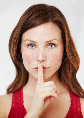 Buy stock photo Portrait of an attractive young woman with her finger on her lips