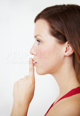 Buy stock photo Profile of an attractive young woman with her finger on her lips