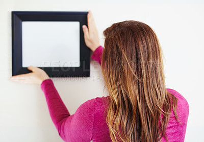 Buy stock photo Rearview shot of a young woman putting up a picture frame