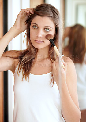 Buy stock photo An attractive young woman applying blusher