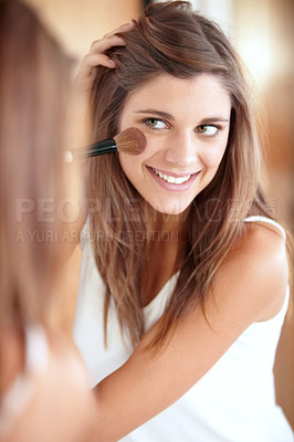 Buy stock photo An attractive young woman applying blush