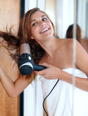 Buy stock photo An attractive young woman blow drying her hair