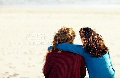 Buy stock photo Rearview shot of two sister's sitting at the beach and looking out to sea