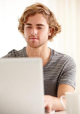Buy stock photo A young man woking on his laptop at home