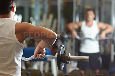 Buy stock photo Rearview shot of a muscular young man working out in the gym