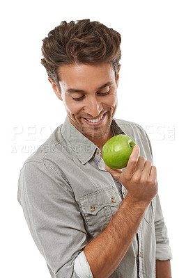 Buy stock photo A handsome young man holding an apple and smiing