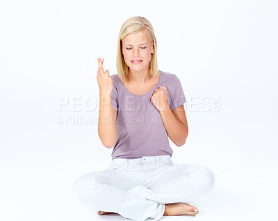 Buy stock photo Sweet young woman sitting down while crossing her fingers