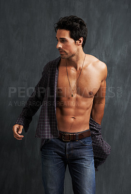 Buy stock photo A muscular young man putting on a shirt