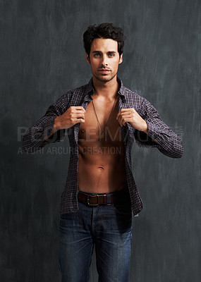 Buy stock photo Portrait of a handsome young man putting on a shirt