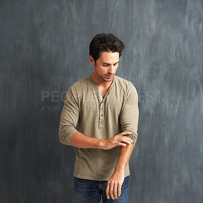Buy stock photo A handsome young man rolling up his sleeves
