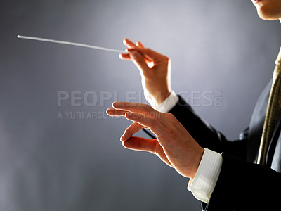 Buy stock photo Cropped image of a male orchestra conductor directing with his baton in concert