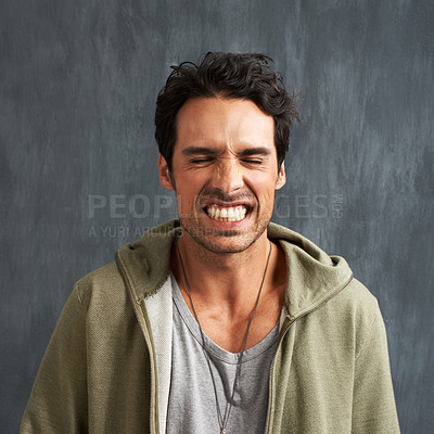 Buy stock photo A young man grimacing with his eyes closed