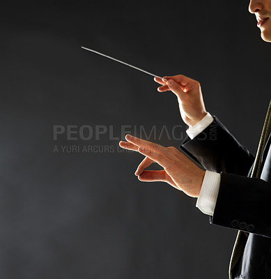 Buy stock photo Cropped image of a male music conductor directing with his baton in concert