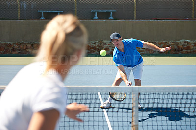 Buy stock photo A male tennis player lobbing the ball over the net