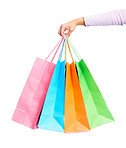 Female's hand holding colorful shopping bags over white