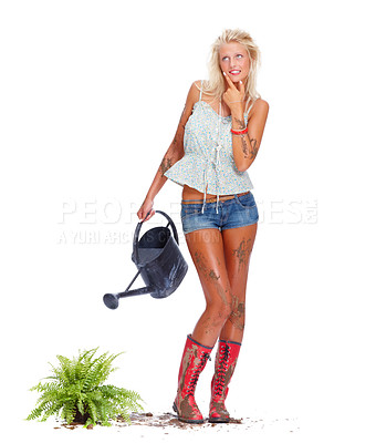 Buy stock photo Sexy young blond babe covered in mud and looking clumsy while watering a plant, isolated on white - copyspace