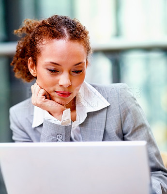 Buy stock photo Pretty young African American business woman busy working on her laptop