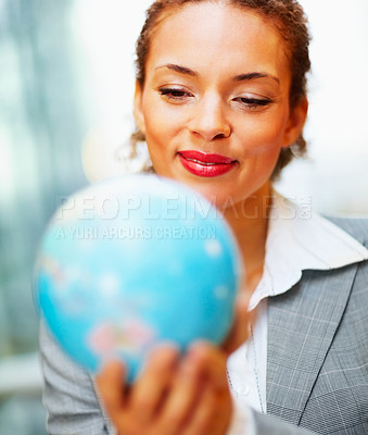 Buy stock photo Pretty young African American business woman holding a globe in her hand