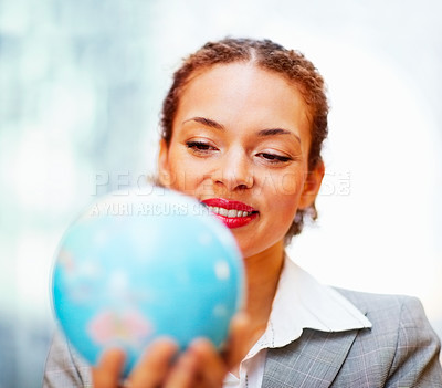 Buy stock photo Young African American business woman holding a globe in her hand, focus on woman