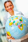Business woman with a globe, focus on globe