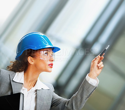 Buy stock photo Young female architect wearing a hardhat pointing upwards with a pen