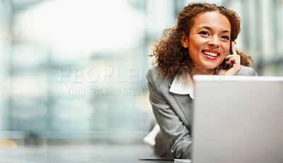 Buy stock photo African American business woman using a laptop on the floor, speaking on the cellphone