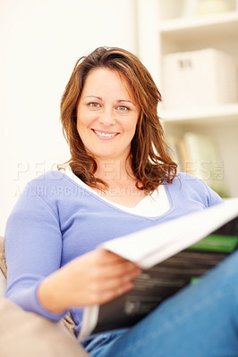 Buy stock photo A happy female reading a newspaper at home