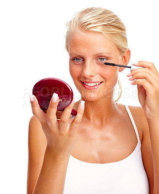Buy stock photo Attractive young model applying mascara using lash brush over white background