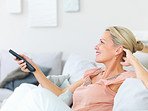 Pretty mature woman watching television while at home