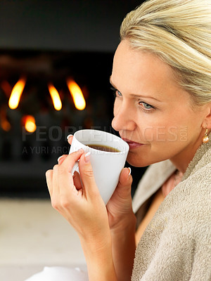 Buy stock photo Closeup of a middle aged woman sipping coffee by a fireplace