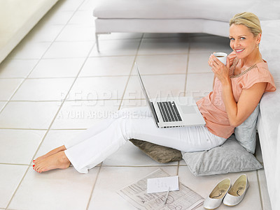 Buy stock photo Cheerful middle aged woman on the floor having coffee while working on a laptop