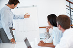 Confident businessman giving presentation to colleagues