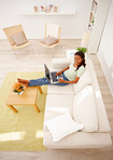 Top view of an African American lady on sofa using a laptop