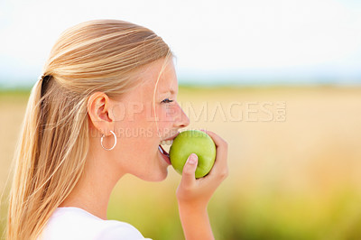 Buy stock photo Cute young female having a apple smiling outdoors