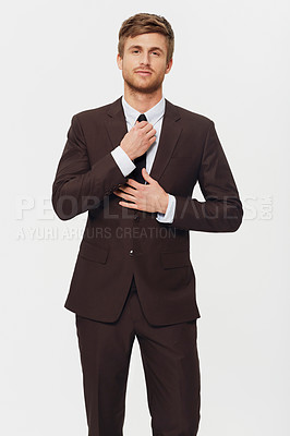 Buy stock photo Studio portrait of a stylish young businessman dressed in a suit and adjusting his tie