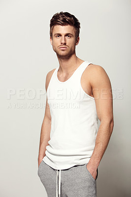Buy stock photo Studio shot of a handsome young man dressed in a tank top and track pants looking at the camera