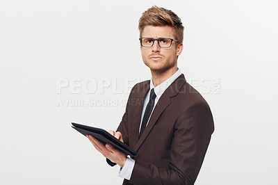Buy stock photo Studio portrait of a stylishly-dressed young businessman holding a digital tablet
