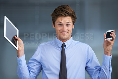 Buy stock photo A smiling young businessman struggling to make a choice between a tablet or a smartphone