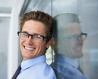 Buy stock photo A handsome young businessman leaning against a glass wall and smiling at you